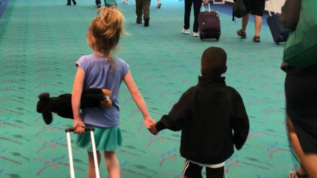 Touching photo shows young children holding hands in airport